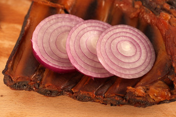 Delicious pork ribs with sliced red onion on wooden plate