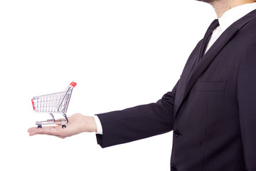 Business man holding a shopping cart, isolated over white backgr