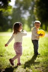 boy and girl playing with yellow ball