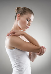 Young woman having joint pain and massaging her elbow