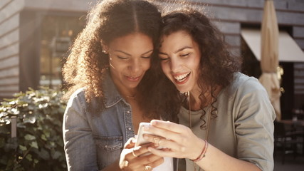 Mixed Race Girl friends look at smart phone together and smile