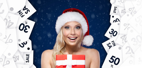 Pretty woman in Christmas cap hands item at a great price