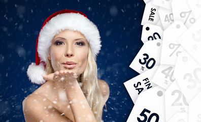 Beautiful woman in Christmas cap blows kiss to all purchasers