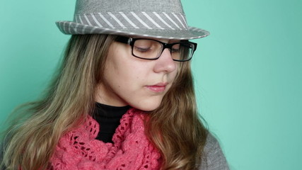 beautiful girl with glasses wearing a hat on a background of tur