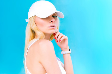 Beautiful girl in a cap on a blue background