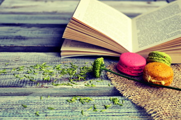 Macaroons with open book on a wooden background