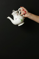 Vintage porcelain teapot on the black background