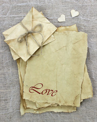 Love letters on antique parchment paper with wooden hearts