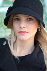 A close up of a beautiful blond woman with a hat, outside