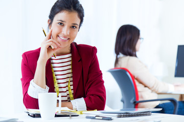 Two young businesswomen working in her office.