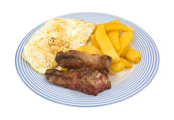 Fried strip steak and eggs with potatoes on blue striped plate