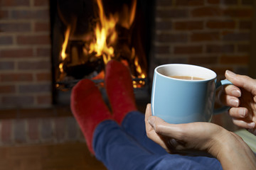 Woman With Hot Drink Relaxing By Fire