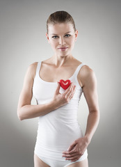 Smiling female holding red heart at breast. Heart protect