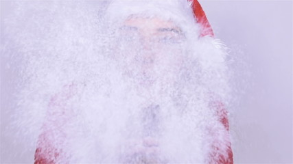Beautiful Santa Claus woman blowing snow from in studio.