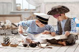 Boys dressed as a pirate captain and read travel map