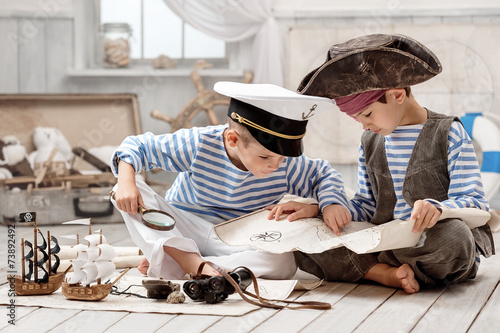 Boys dressed as a pirate captain and read travel map - 73892492
