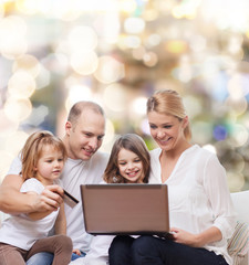 happy family with laptop computer and credit card