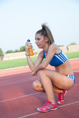 Athletic fitness girl holding energy drink