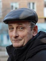 Пожилой мужчина в зимней одежде смотрит с улыбкой