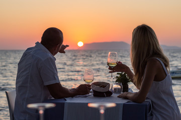 Couple drinking wine at beach restaurant  on sunset