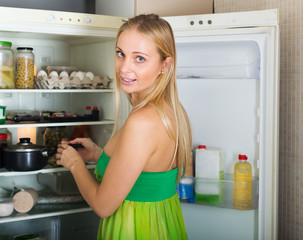girl near opened refrigerator in kitchen at home