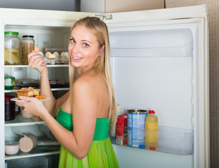 Woman eating cake from fridge