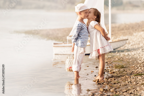 Boy with girl walking along the shore of the lake - 73895249