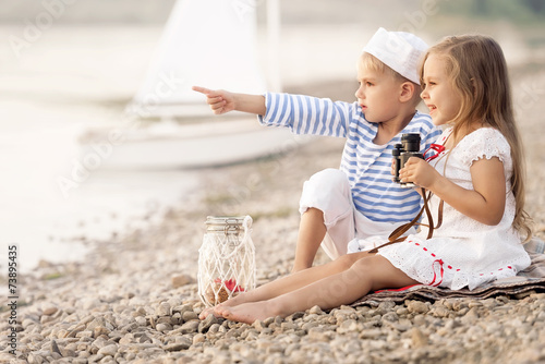 Boy with a girl sitting on the beach - 73895435