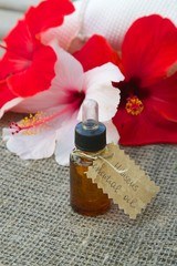 A dropper bottle of hibiscus essential oil.