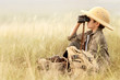 Boy looking through binoculars in a thick gray grass - 73896024