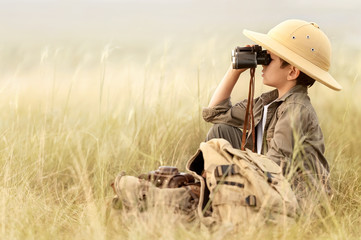 Boy looking through binoculars in a thick gray grass