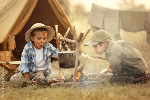 Two of children sitting around the campfire travelers - 73896060