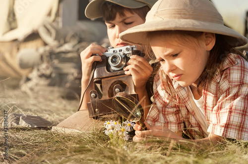 Two children explore insects and plants on earth - 73896237
