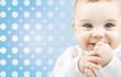 smiling baby boy face over blue polka dots