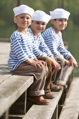 Portrait of boys sailors sitting on the pier of a mountain lake