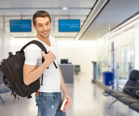 smiling student with backpack and book at airport