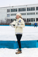 Smiling girl with fads on ice skating rink