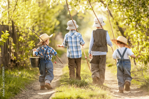 Boys go fishing with fishing rods on a rural street - 73899005