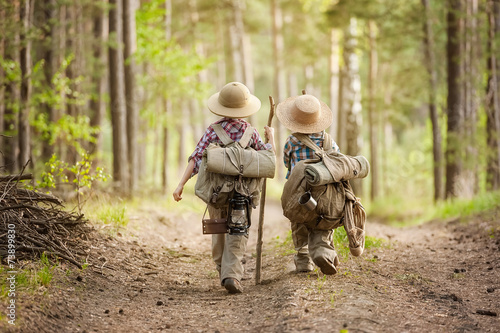Boys on a forest road with backpacks