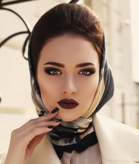 portrait of beautiful elegant girl in beige coat and silk scarf
