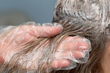beautician applying hair dye on female customer's hair