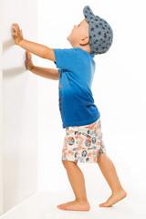 Blond boy pushing he wall white bacground