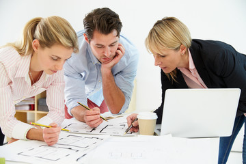 Architects Planning Layout Of Empty Office Space