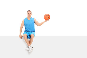 Basketball player sitting on a blank billboard