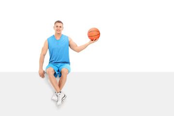 Basketball player sitting on a blank billboard