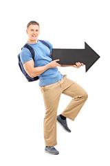 Male student holding a big black arrow