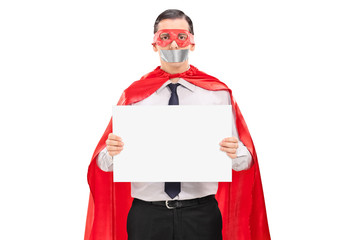 Hostage in superhero costume holding blank banner