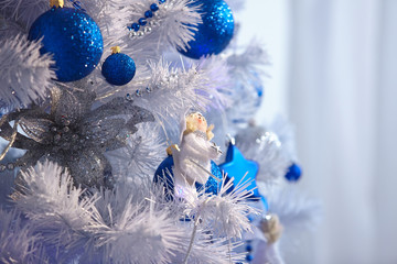 White Christmas tree with a blue toy, garlands, beads