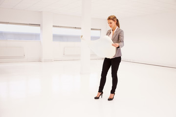 Female Architect Planning Layout Of Empty Office Space
