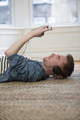 Caucasian man lying on the floor at home reading his tablet PC.